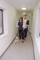 Two residents of homeless hostel walking along corridor with pet dog,
