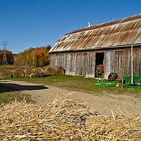 Bales of straw and hay outside of a barn. the nose of a tractor is just peeking out of the barn's open door.