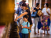 11 AUGUST 2016 - BANGKOK, THAILAND: People make merit by donating money at Wat Pho in Bangkok. Wat Pho (the Temple of the Reclining Buddha), is formally known as Wat Phra Chetuphon. It's one of the largest temple complexes in Bangkok and best known for the giant reclining Buddha that measures 46 metres long and is covered in gold leaf. There is also a large ordination hall and the best known massage school in Thailand on the temple grounds.          PHOTO BY JACK KURTZ