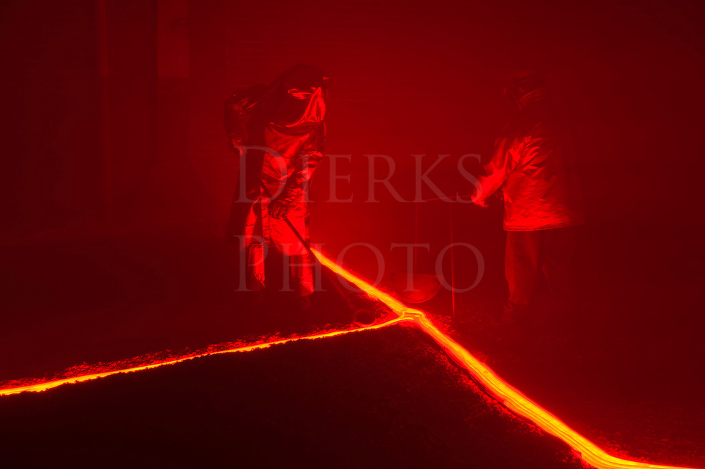 Pouring hot, glowing, molten iron across an earthen floor by two steelworkers, two reenactors recreating a metalurgical process.