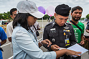 "24 JUNE 2014 - BANGKOK, THAILAND: A Thai police officer (right) talks to a poet  (left) about her poem after she read it aloud at a meeting of the Monsoon Poets Society in Bangkok. Members of the ""Monsoon Poets Society"" gathered in front of the Anantasamakom Throne Hall Tuesday to pay homage to the People's Party, a Siamese (Thai) group of military and civil officers (which became a political party) that staged a bloodless coup against King Prajadhipok (Rama VII) and changed Thailand (then Siam) from an absolute monarchy to a constitutional monarchy on 24 June 1932. Since the coup against the civilian government on 22 May, the ruling junta has not allowed political gatherings. Although police read the poems, they did not arrest any of the poets or make any effort to break up the gathering.     PHOTO BY JACK KURTZ"