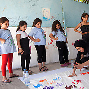 In Ein El-Hilweh refugee camp, home to 75.000 Palestinians. Girls wash their hands after having been hand painted. It is summer break in the UNWRA school and Naba'a runs Play and Learn sessions in the empty school for vulnerable children. They aim is to give them a safe space to express themselves with out fear of repression. Developmental Action Without Borders(Naba'a) work in Palestinian refugee camps across Lebanon to help children in the camps.  The camps are densely over-crowded and many of the children are 4th generation refugees living in Lebanon with no citizenship or rights and under immense pressure. Naba'a is a mix of Palestinians and Lebanese and aim to give children a sense of security and freedom to express their needs and rights.Naba'a operates in communities governed by a multitude of political parties and religious groups and Naba'a keeps a strict independed line from any affiliation with any groups.
