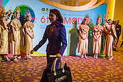 24 JUNE 2014 - BANGKOK, THAILAND: A conference participant walks past greeters at the the 6th Asian Ministerial Conference on Disaster Risk Reduction (AMCDRR). The AMCDRR started in Bangkok on June 24. The first of the biennial conferences was held in Beijing in 2005 after the 2004 Asian Tsunami and H5N1 Bird Flu epidemic of 2004. The conference this year in Bangkok will focus on possible disasters related to climate change, sustainable development, and managing public private partnerships for disaster risk.     PHOTO BY JACK KURTZ