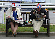 © Licensed to London News Pictures. 02/06/2012. London, UK. A couple read copies of newspapers on a bench. HRH Queen Elizabeth at The Investic Derby Festival today 2nd June 2012. The Royal Jubilee celebrations. Great Britain is celebrating the 60th  anniversary of the countries Monarch HRH Queen Elizabeth II accession to the throne this weekend Photo credit : Stephen Simpson/LNP