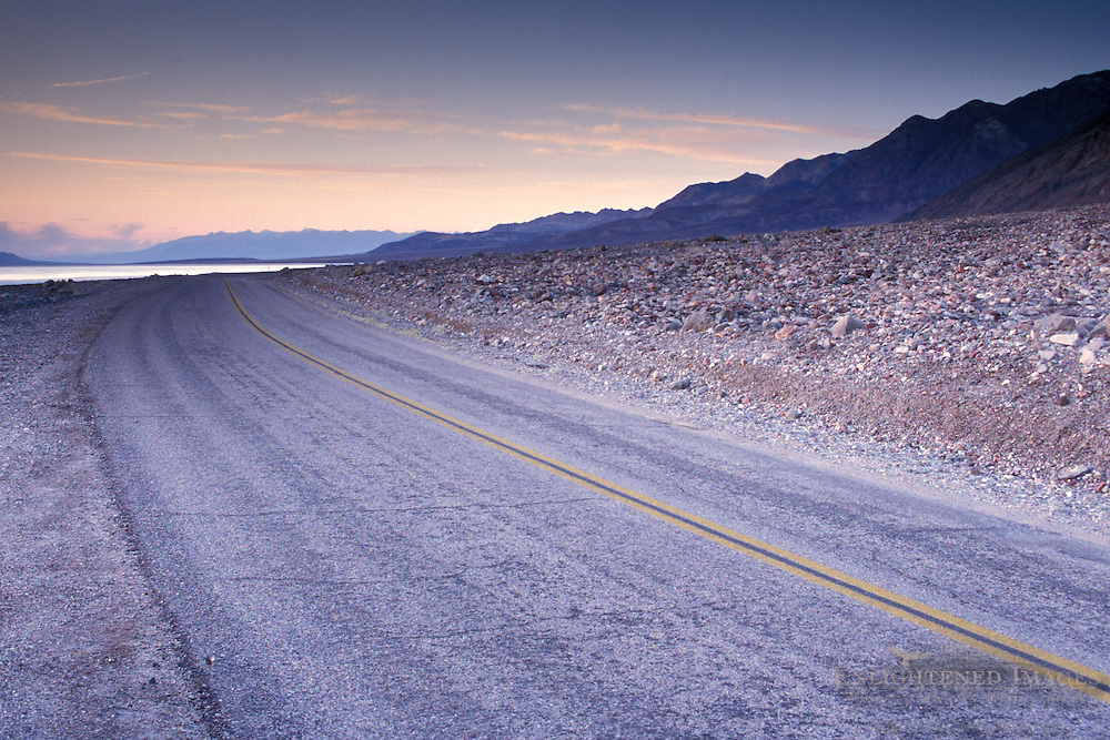 Empty asphalt road below mountains in evening light, Death Valley National Park, California