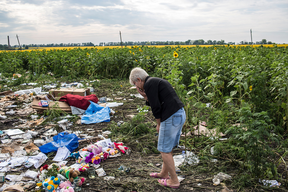 RASSIPNOYE, UKRAINE - JULY 19: A woman looks at debris from Malaysia Airlines flight MH 17 which landed in a field of sunflowers on July 19, 2014 in Rassipnoye, Ukraine. Malaysia Airlines flight MH17 was travelling from Amsterdam to Kuala Lumpur when it crashed killing all 298 on board including 80 children. The aircraft was allegedly shot down by a missile and investigations continue over the perpetrators of the attack. (Photo by Brendan Hoffman/Getty Images) *** Local Caption ***