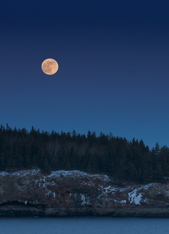 Visitors to Acadia National Park in the winter will be rewarded with vistas of snow-accented pink granite shorelines and the quiet beauty of frozen lakes without the crush of a summer crowd. Here, a full moon rises over Great Head Peninsula, seen from Park Loop Road.