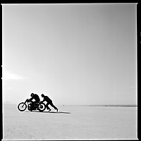 Riders push a broken down motorcycle on the starting line at El Mirage Dry Lake near Los Angeles.