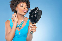 Attractive African American woman puckering while looking in mirror over colored background