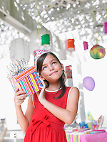 Portrait of girl (7-9) holding birthday present at party