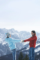 Couple holding hands standing face to face in mountains side view