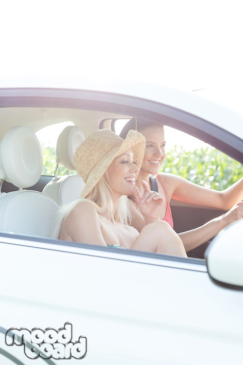 Young female friends enjoying road trip in car on sunny day