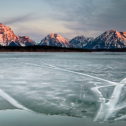 The sunrises over the Tetons and an ice covered Jackson Lake in Grand Teton National Park, Wyoming