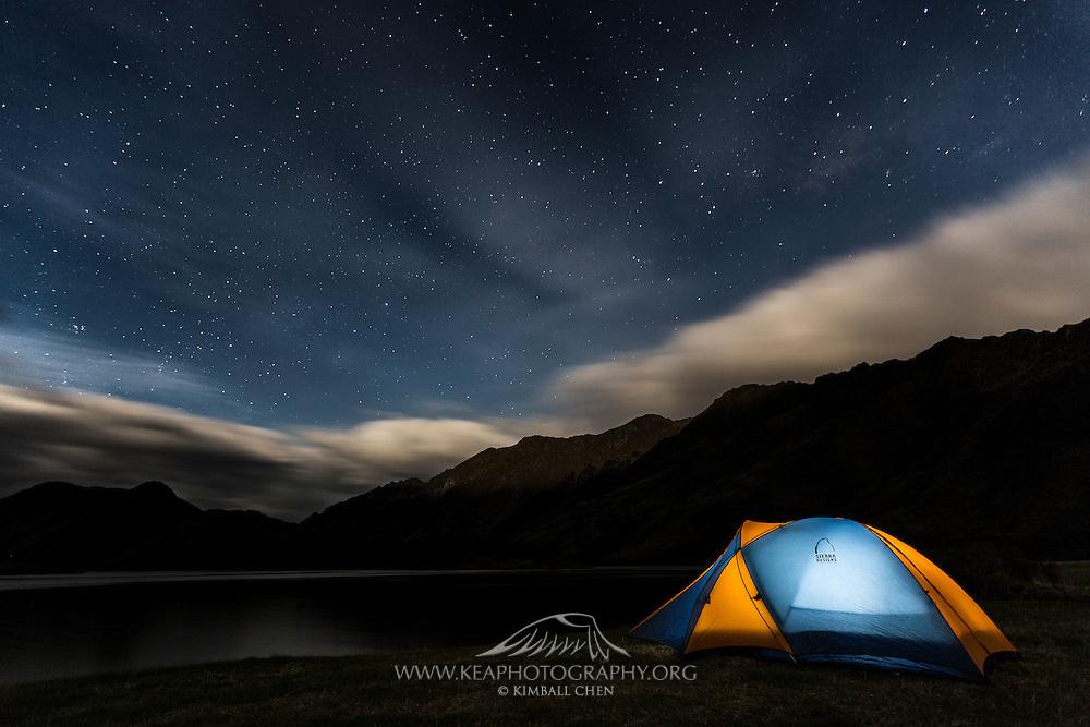 A rising full moon begins to illuminate the mountain range at Moke Lake, near Queenstown.