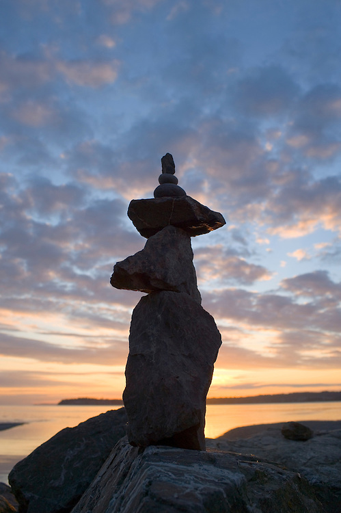 Silhouette of stack of balanced rocks at sunset with ocean.