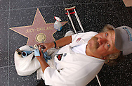 HOLLYWOOD, CA.  John Peterson pauses while cleaning the brass nameplates of the stars along the Walk of Fame on Hollywood Boulevard in Hollywood, CA on Thursday, July 29, 2004.  © CHET GORDON / THE IMAGE WORKS