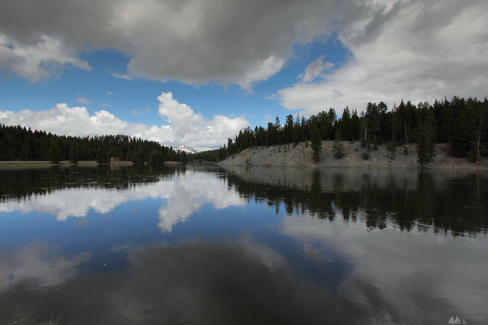 Grey & white clouds reflect in the Yellowstone River, in Yellowstone National Park, Wyoming, USA