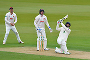 Rilee Rossouw of Hampshire hits the ball over the boundary for six runs watched by Sir Alastair Cook of Essex and Dan Lawrence of Essex during the first day of the Specsavers County Champ Div 1 match between Hampshire County Cricket Club and Essex County Cricket Club at the Ageas Bowl, Southampton, United Kingdom on 5 April 2019.