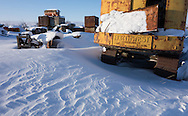 Drifts of snow cover old equipment and vehicles in Umiat on Alaska's North Slope. Exploratory oil drilling has been on-going since the 1950s.