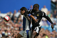 Photo: Lee Earle.<br /> Portsmouth v Wigan Athletic. The Barclays Premiership. 09/09/2006. Portsmouth's Dejan Stefanovic (L) holds off Emile Heskey.