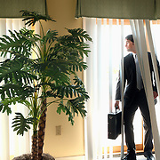 Businessman poses behind blinds and curtains (model D.Mciver)