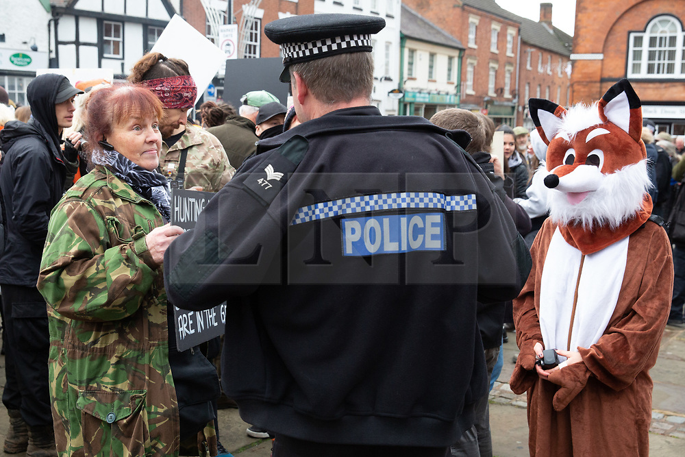 © Licensed to London News Pictures. 01/01/2019. Atherstone, North Warwickshire, UK. Police keeping a careful watch on the anti hunt protestors at the Atherstone Hunt meet in the Market Square, Atherstone Town Centre, Warwickshire. The traditional New Year's Day Hunt starts at Noon with speeches and a drink for the Huntsmen and women. Riders of all ages took part in the meet and there were protests from Anti Hunt protestors who had positioned themselves in the centre of the Market Square. The Hunt then formed up and rode from the town centre passing huge New Year's Day crowds that had come to see the spectacle. Photo credit: Dave Warren/LNP