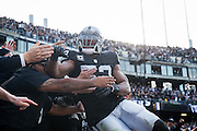 Oakland Raiders defensive end Khalil Mack (52) celebrates a touchdown with fans in the Black Hole against the Carolina Panthers at Oakland Coliseum in Oakland, Calif., on November 27, 2016. (Stan Olszewski/Special to S.F. Examiner)