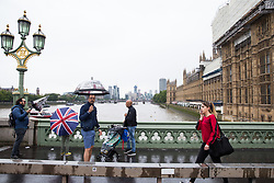 London, UK. 19 July, 2019. Tourists with umbrellas brave heavy rain showers on Westminster bridge.