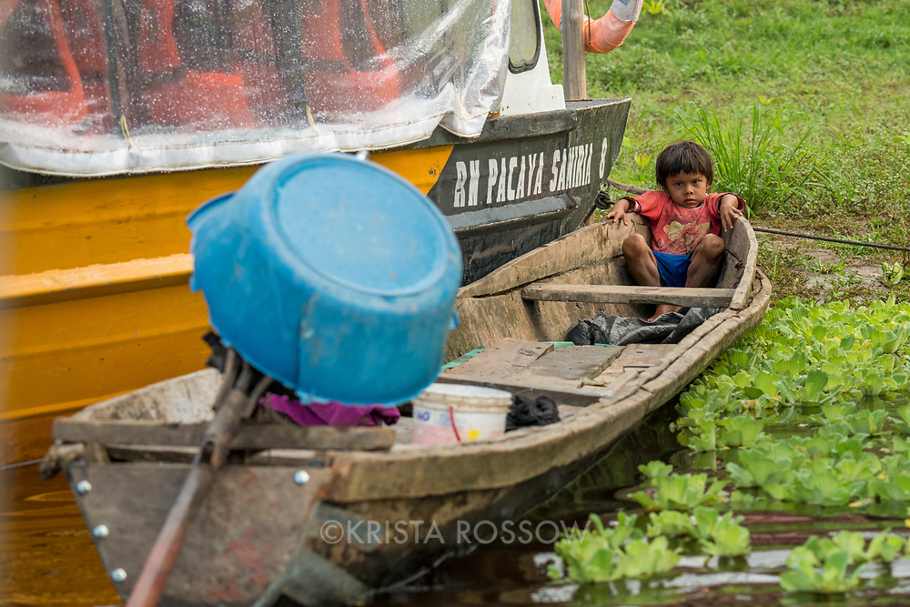 A young boy sits in an anchored canoe on the Yanayacu River in the headwaters of the Amazon River in Peru's Pacaya-Samiria National Reserve.