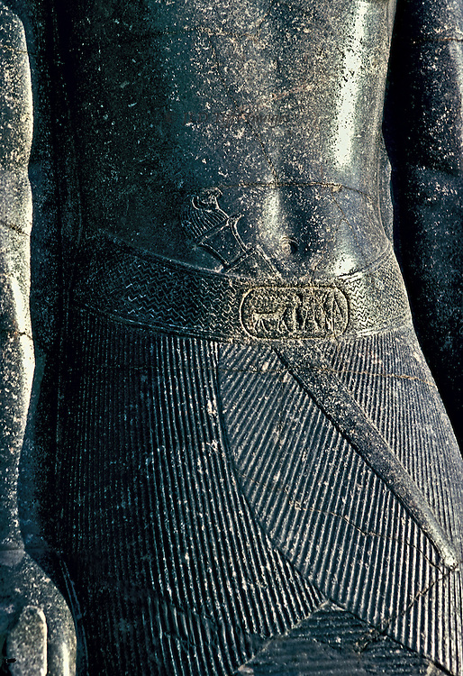 Pharaoh's flat basalt tummy ;  Detail of a black basalt statue in the Luxor museum. No belly fat.