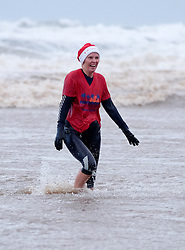 © Licensed to London News Pictures. <br /> 01/01/2017. <br /> Saltburn by the Sea, UK.  <br /> <br /> A woman wearing a onesie paddles in the cold waters of the North sea as she takes part in the annual New Year Day dip at Saltburn beach.<br /> <br /> The event helps to raise money for the Saltburn Animal Rescue Association.<br /> <br /> Photo credit: Ian Forsyth/LNP