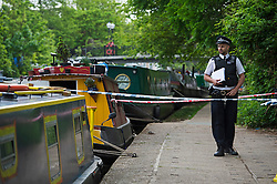 © London News Pictures. 11/05/2015. A police officer stands next to a cordoned off areaalong the tow path of the canal at Little Venice in West London where a body has been found in a suitcase. The discovery was made on the Grand Union Canal near Delamere Terrace. Photo credit: Ben Cawthra/LNP