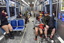 """© Licensed to London News Pictures. 07/01/2018. CHICAGO, USA.  Participants take part in the annual """"No Pants Subway Ride"""", a fun event taking place both in Chicago and worldwide, where people ride the subway wearing no trousers.  With Chicago experiencing an extreme cold snap currently, temperatures made taking part more challenging.  Photo credit: Stephen Chung/LNP"""