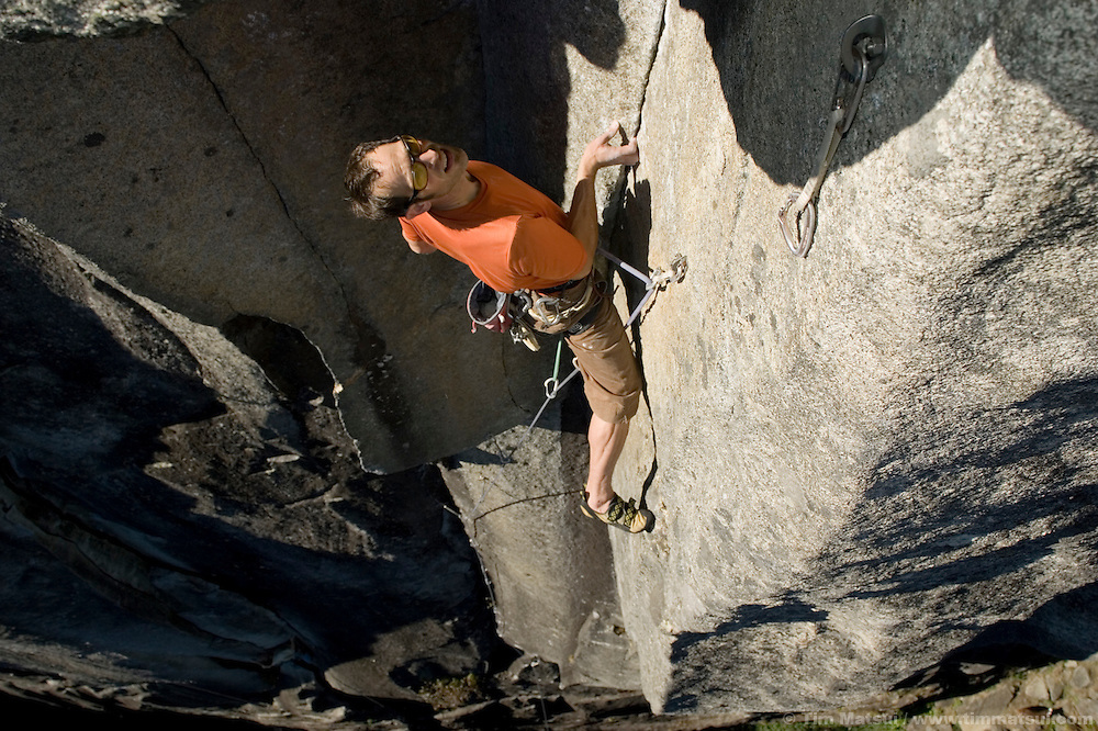 A man climbing steep granite rock in Index, Washington, near Seattle.