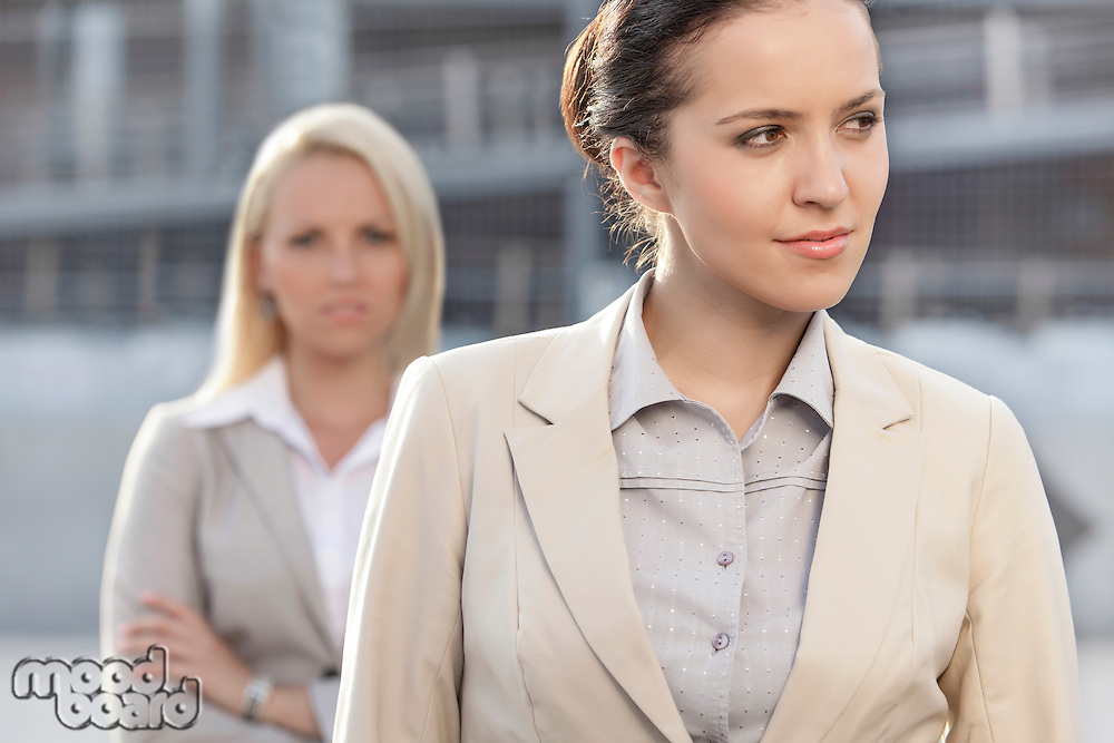 Young businesswoman looking away with female colleague in background