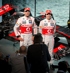 """© London News Pictures. 31/01/2013 . Woking, UK.  Team McLaren Mercedes drivers Jenson Button (left) and Sergio """"Checo"""" Perez (right) pose for photographers at the unveiling of the new MP4-28 Formula 1 car at the McLaren Technology Centre in Woking, Surrey, on  Thursday, Jan. 31, 2013. Photo credit : Ben Cawthra/LNP"""