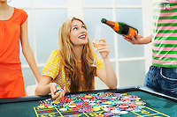 Young woman celebrating with friends at roulette table