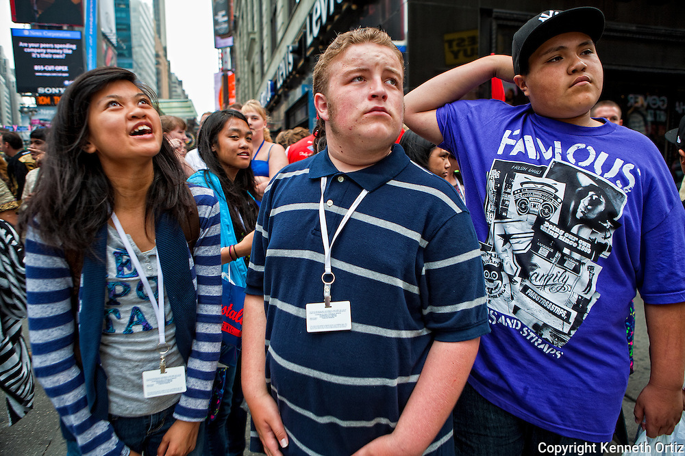 Teenagers at the corner of 44th Street and 7th Avenue in the heart of Time Square, New York City looking in different directions.