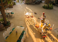 Looking down on a courtyard at Manvar Resort where a woman is having a meal served while sitting in a shaft of sunlight racking across the courtyard. Outside Jodhpur, India.