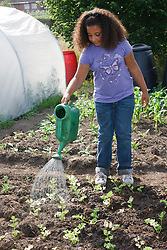 Girl watering plants with watering can