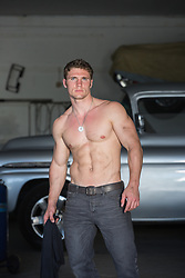 shirtless muscular man in an auto repair shop