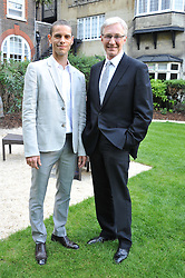 Left to right, ANDRE PORTASIO and PAUL O'GRADY at a reception hosted by the Friends of the Castle of Mey held at the Goring Hotel, Beeston Place, London on 22nd May 2012.