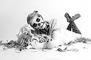 female lying down shot with skeleton makeup holding skeleton shot in black and white on white background