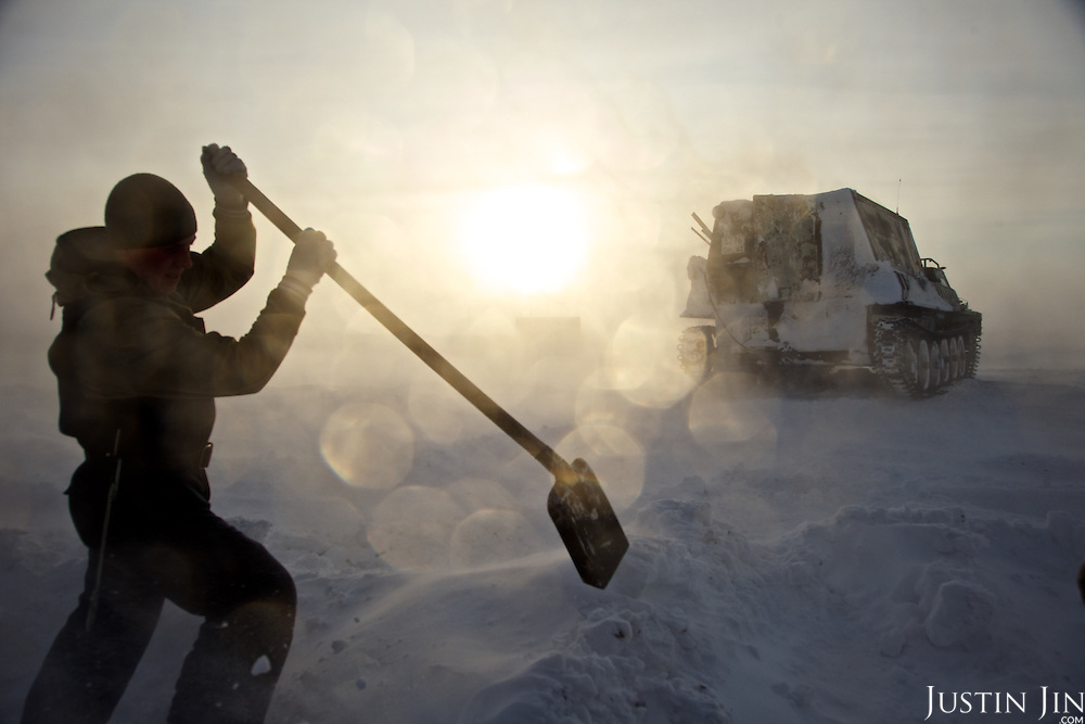 """Workers dig snow in the colony set up by oil and gas prospecting company """"Siesmorevzedka"""" in the Arctic tundra. Typically, they work in the cold, isolated Arctic tundra for the entire winter, returning to civilisation only in spring."""
