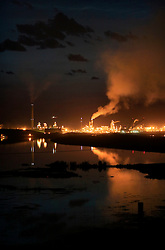 CANADA ALBERTA FORT MCMURRAY 20JUL09 - Night view of Syncrude upgrader plant north of Fort McMurray, northern Alberta, Canada...The tar sand deposits lie under 141,000 square kilometres of sparsely populated boreal forest and muskeg and contain about 1.7 trillion barrels of bitumen in-place, comparable in magnitude to the world's total proven reserves of conventional petroleum. Current projections state that production will  grow from 1.2 million barrels per day (190,000 m³/d) in 2008 to 3.3 million barrels per day (520,000 m³/d) in 2020 which would place Canada among the four or five largest oil-producing countries in the world...The industry has brought wealth and an economic boom to the region but also created an environmental disaster downstream from the Athabasca river, polluting the lakes where water and fish are contaminated. The native Indian tribes of the Mikisew, Cree, Dene and other smaller First Nations are seeing their natural habitat destroyed and are largely powerless to stop or slow down the rapid expansion of the oil sands development, Canada's number one economic driver...jre/Photo by Jiri Rezac / GREENPEACE..© Jiri Rezac 2009