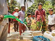 03 JUNE 2016 - SIEM REAP, CAMBODIA: Villagers wait as their water jugs are filled at a water distribution point in Sot Nikum, a village northeast of Siem Reap. Wells in the village have been dry for more than three months because of the drought that is gripping most of Southeast Asia. People in the community rely on water they have to buy from water sellers or water brought in by NGOs. They were waiting for water brought in by truck from Siem Reap by Water on Wheels, a NGO in Siem Reap. Cambodia is in the second year of  a record shattering drought, brought on by climate change and the El Niño weather pattern. There is no water to irrigate the farm fields and many of the wells in the area have run dry.     PHOTO BY JACK KURTZ