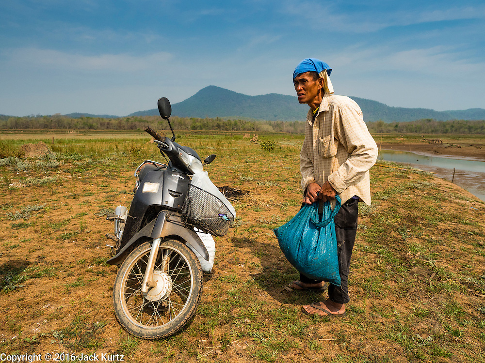 02 APRIL 2016 - NA SAK, LAMPANG, THAILAND:  A man walks back to his motorscooter in what used to be Sobjant village. The village of Sobjant in Na Sak district in Lampang province was submerged when the Mae Chang Reservoir was created in the 1980s. The village was relocated to higher ground a few kilometers from its original site. The drought gripping Thailand drained the reservoir and the foundations of the Buddhist temple in the original village became visible early in 2016. Thai families come down to the original village to pray in the ruins of the temple and look at what's left of the village. This is the first time in more than 30 years that this area has not been under two meters of water.     PHOTO BY JACK KURTZ
