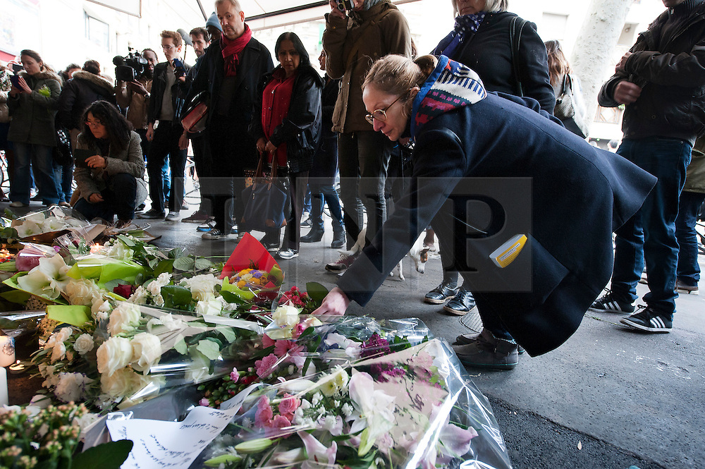 © London News Pictures. 14/11/2015. People lay flowers and and light candles at La Bell Equipe, Rue de Charonne where 18 people lost their lives, the day after multiple terror attacks on the french capital. Photo credit: Guilhem Baker/LNP