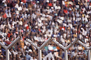 Orlando Soccer Stadium fans during a Pirates vs. Durban game. Like many soccer stadiums around the world, the playing field is securely fenced to protect the team from the fans. Soweto, South Africa. Material World Project.