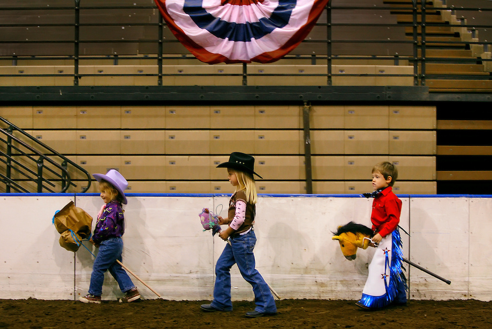 "Breanna Robbins, left, Jaycie Rauch, center, and Drake Israel, right, walked around the show ring at the American Royal's Hale Arena  during the stick horse ""competition"" at the Quarter Horse Show. All the entrants received blue ribbons for their equestrian skills."